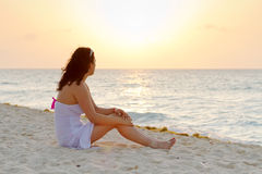 Watching sunrise on the beach. Beautiful woman watching sunrise on the beach Stock Image