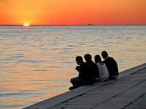 Watching the Sunset. Four people sitting watching the sunset Royalty Free Stock Photography