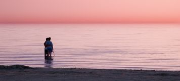 Watching sunset. Couple standing in water watching the sunset Royalty Free Stock Photo