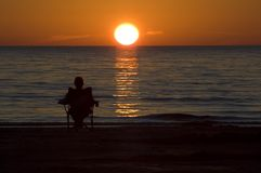 Watching the sunset. Woman sitting watching a colourful sunset over the lake Stock Photo