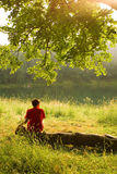 Watching sunset. Young man sitting alone on a log, under a tree, looking down to the water in late afternoon Royalty Free Stock Images