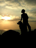 Watching the sunset. Silouette of kid and his dog,watching the sunset stock images