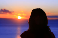 Watching the Sunset. Female watching the sun set across the ocean Stock Photography