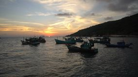 Watching sunset on the beach with Vietnamese traditional fishing boats floating on scenic blue sea in background. Timelapse video. Silhouettes of Vietnamese stock video footage