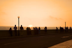 Watching the Sunset in Miraflores, Lima, Peru. LIMA, PERU - MARCH 11, 2012: Unidentified people watching the sunset over the Pacific ocean from the pavement Stock Photos