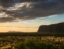 Watching the Sunset on Uluru. Formerly known as Ayers Rock, in Australia, I was struck by the golden light and the beauty of the scene.  Kata Tjuta lies Royalty Free Stock Image