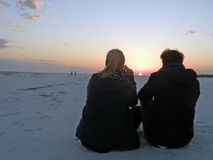 Watching the sunset. A young couple watches the sunset on the beach in Mexico Beach Florida Royalty Free Stock Photo