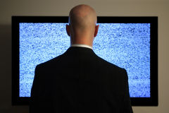 Watching television. A man watching a blank or static screen of his television Stock Photo