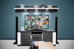 Watching television in modern TV room. Hand holding remote Stock Images