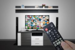Watching television in modern TV room. Hand holding remote Royalty Free Stock Image