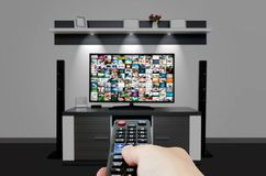 Watching television in modern TV room. Hand holding remote Stock Photos