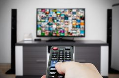 Watching television in modern TV room. Hand holding remote. Control Stock Photo