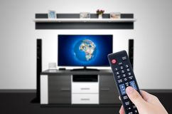 Watching television in modern TV room. Hand holding remote Royalty Free Stock Photo