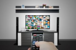 Watching television in modern TV room. Hand holding remote Royalty Free Stock Photos