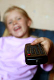 Watching TV. Little girl and remote control Royalty Free Stock Image