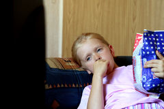 Watching TV. Little girl lying, eating popcorn and watching TV Royalty Free Stock Photography