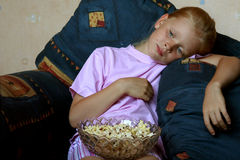 Watching TV. Little girl lying, eating popcorn and watching TV Stock Photos