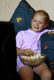 Watching TV. Little girl lying, eating popcorn and watching TV Stock Photo