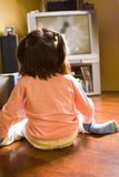 Watching TV. Rear view of little girl sitting on the floor and watching cartoons on TV at home Royalty Free Stock Images