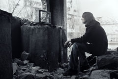 Watching TV. Homeless man watching broken TV-set in the ruined interior. Shallow depth of field due to the tilt lens for movie effect Stock Images