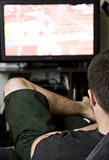 Watching tv. Photo of a young man watching tv Royalty Free Stock Image