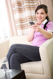 Watching tv. Young adult woman watching tv at home stock photography