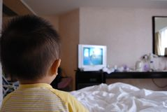 Watching TV. A chinese boy is watching the TV in home Royalty Free Stock Images