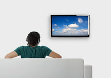 Watching tv. Rear view from a young man seated on the couch watching tv Royalty Free Stock Photos
