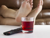 Watching TV. Persons feet up on coffee table while watching TV with remote control and drink on table Royalty Free Stock Photo