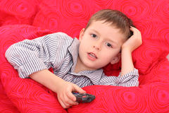Watching TV. 5-6 years old boy watching TV in bed Stock Images