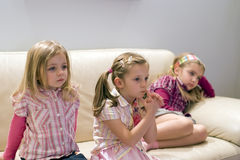 Watching TV. Three cute, little girls sitting on a sofa, watching television Stock Photo