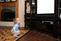 Watching TV. A little boy squats down in front of the television and watches. The screen is blank for text or pictures to be inserted Stock Photos