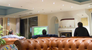 Watching TV. Three men watching soccer on the TV in a hotel lounge royalty free stock photo