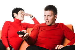Watching TV. Young couple is watching TV. The man is looking at the screen and enjoys the program (maybe some sport), while the woman looks bored Royalty Free Stock Images