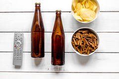 Watching TV with chips, beer and remote control on white background top view Royalty Free Stock Images