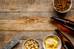 Watching TV with chips, beer and remote control on wooden background top view mock up Royalty Free Stock Image