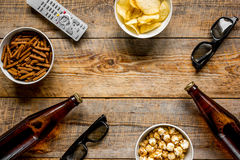 Watching TV with chips, beer and remote control on wooden background top view mock up Royalty Free Stock Photos