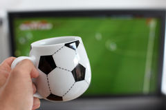 Watching TV with a coffee mug Royalty Free Stock Images