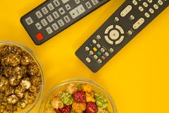 Watching TV concept. Weekend, Leisure, Lifestyle Concept with caramel popcorn and TV remote controls on a bright one-colore yellow background, flat lay Royalty Free Stock Image