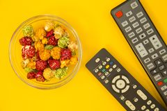 Watching TV concept. Weekend, Leisure, Lifestyle Concept with caramel popcorn and TV remote controls on a bright one-colore yellow background, flat lay Royalty Free Stock Images