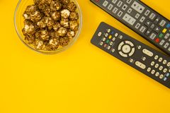 Watching TV concept. Weekend, Leisure, Lifestyle Concept with caramel popcorn and TV remote controls on a bright one-colore yellow background, flat lay Royalty Free Stock Photography