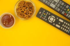 Watching TV concept. Weekend, Leisure, Lifestyle Concept with two TV remote controls, salty pretzels and ketchup on a bright one-colore yellow background, flat Royalty Free Stock Image