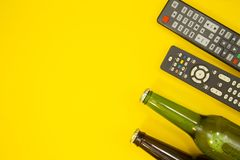 Watching TV concept. Weekend, Leisure, Lifestyle Concept with two TV remote controls and two bottles of beer on a bright one-colore yellow background, flat lay Royalty Free Stock Images