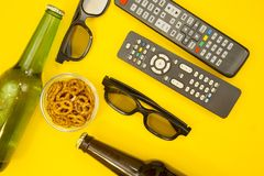Watching TV concept. Weekend, Leisure, Lifestyle Concept with two TV remote controls, two pairs of 3d glasses, beer and snacks on a bright one-colore yellow Stock Images
