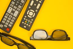 Watching TV concept. Weekend, Leisure, Lifestyle Concept with two TV remote controls, two pairs of 3d glasses on a bright one-colore yellow background, flat lay Stock Photos