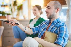 Watching TV. Couple relaxing at home watching television together Stock Images