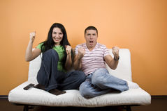 Watching TV at favorite sport team. Happy couple home watching TV their favorite sport team or favorite match over television and they exclaim gladly :GOAL,check stock photo