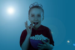 Watching tv. The little girl is watching tv and eating popcorn Royalty Free Stock Photos