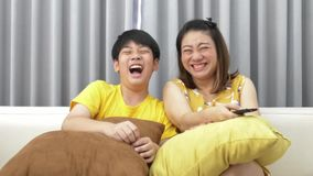 Watching TV lying on the couch. asian Mom and son watch TV together and smile. Mom switches channels. slow motion stock footage