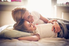 Watching TV with Mom in bed. Little girl. Morning stock photo